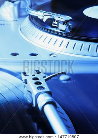Turntable player with musical vinyl record. Useful for DJ nightclub and retro theme. Saturated blue color