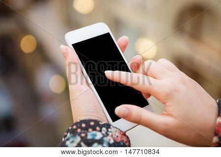 Girl using mobile application or app on big trendy white smart phone touch screen.Blank black screen.Place your text on cut out area.