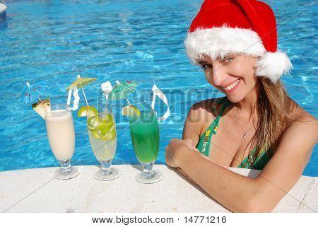 Girl in Santa hat near the swimming pool