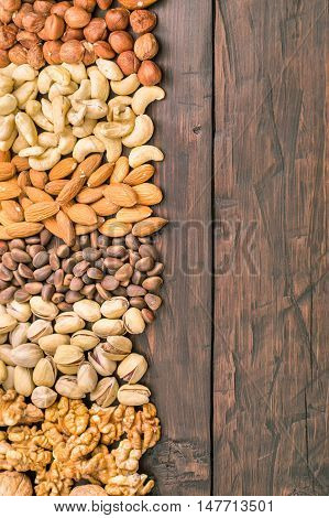 Variety nuts background from left side of old wooden table with copy space