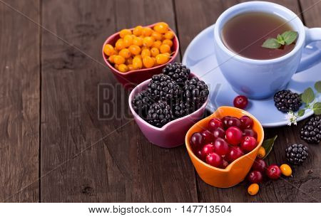 Blackberry, cranberry and buckthorn with cup of tea