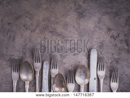 Vintage silverware from bottom side of grunge background top view matte color