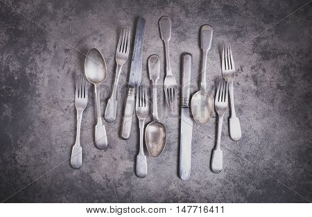 Vintage silverware on grunge background top view matte color