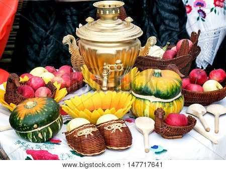 On the table is a samovar is a beautiful Golden brown close to wicker baskets of ripe apples pumpkins wooden spoons.