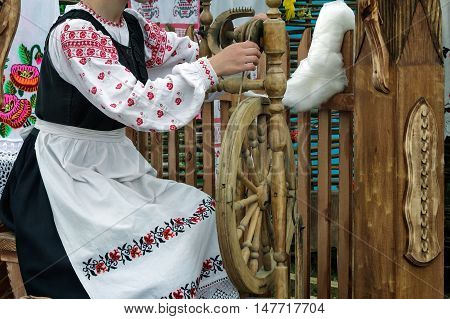 Near an old spinning wheel sits a young woman in national costume and produces yarn.