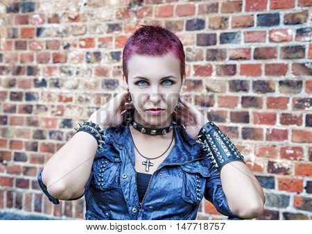 portrait of girl punk near a brick wall outdoor closeup