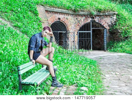 punk girl sitting on the bench near old abandoned castle