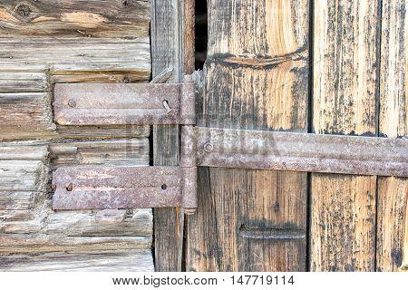 metal door hinge on the old wooden gate closeup