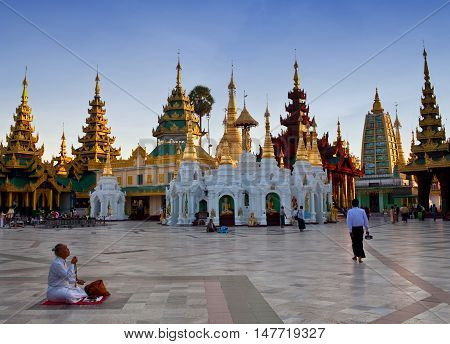 YANGON, MYANMAR - JANUARY 3, 2011: Pilgrim praying in Shwedagon in Yangon, Myanmar.