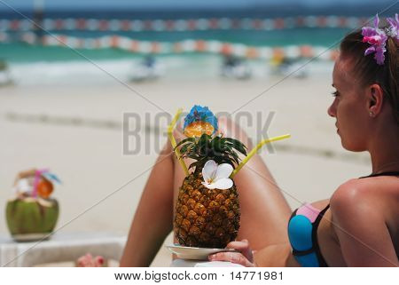 Girl with tropical cocktail on the beach