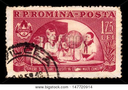 ROMANIA - CIRCA 1954: A stamp printed in Romania shows young pioneers looking at a globe, circa 1954