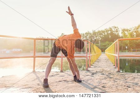Young sporty man bending down and doing stretching exercise