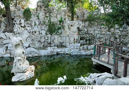 A large rock with a small pond within the traditional chinese garden on the Kong Family mansion property in the city of Qufu lcoated in Shandong Province China.