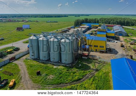 Novikova, Russia - June 18, 2015: Aerial view onto modern machine yard of agricultural firm Russian Field. Corn dryer silos standing in machine yard. Tyumen region