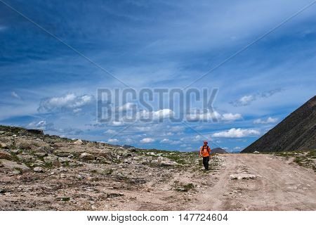 ALTAY, RUSSIA - JULY 23, 2007: Hiker walking on the road to Ukok plateau in the Altay Mountains Russia