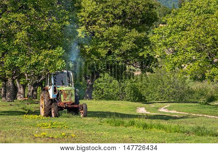 Old tractor on the grass field. Old tractor cultivate.