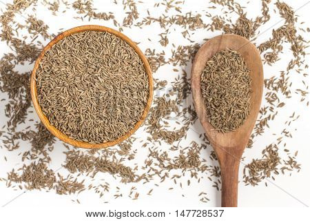 Cumin seeds into a bowl isolated in white background