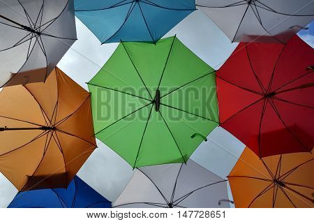 Opened colorful umbrellas with parts of cloudy sky as a background
