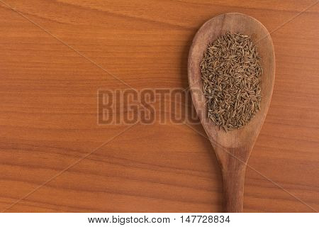 Cumin seeds into a spoon over a wooden table