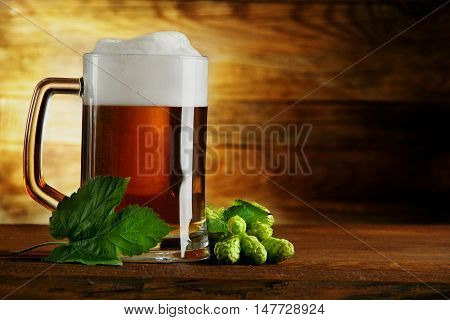 mug of beer and hops and leaf.on a wooden table