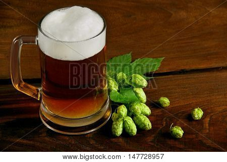 mug of beer and hops.selective focus.on a wooden table