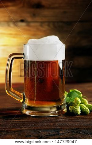 mug of beer and hops.Vertical shot.on a wooden table