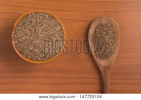 Cumin seeds into a bowl over a wooden table