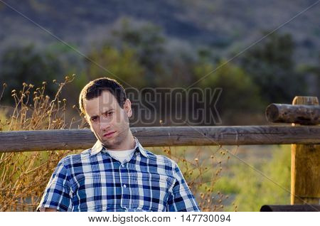 Man with a bored, indifferent expression slouching sitting in a field.