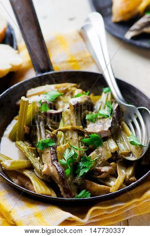 stewed celery with cepes in a vintage frying pan. selective focus