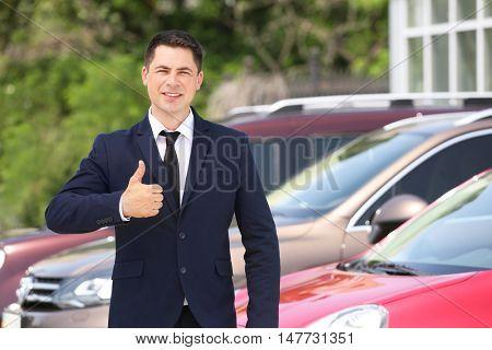 Car dealer on new cars background
