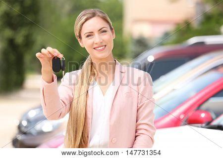 Female car dealer with keys on parking