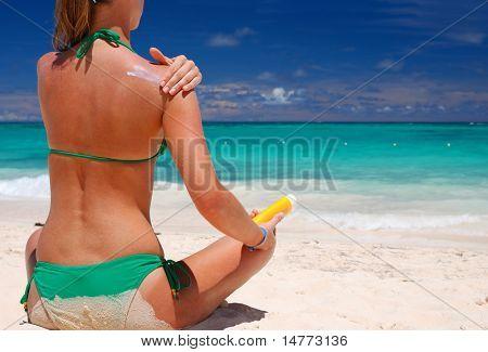 Mujer tan aplicar Crema de protección solar