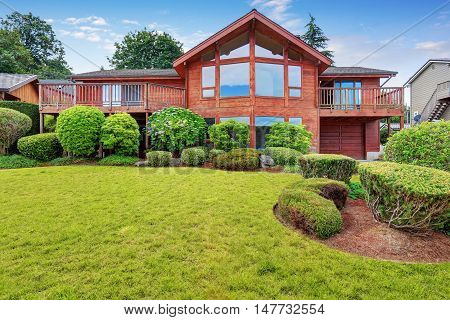 Luxury House Exterior With Wooden Panel Trim, Garage And Well Kept Garden Around.