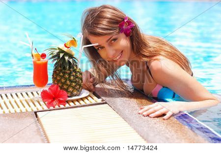 Girl in tropical pool with cocktail