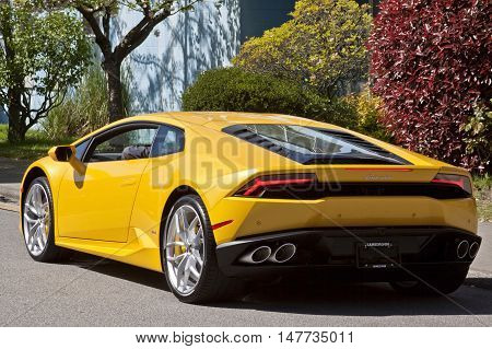 Vancouver, BC - April 20, 2015 -  On display in front of Lamborghini Vancouver, 1720 West 2nd Avenue, Vancouver, BC. Beautiful shot of a gorgeous yellow Lamborghini from the rear, with reddish, green/yellow bushes, trees and a blueish grey wall as a compl
