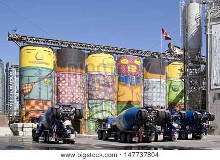 Vancouver, BC - April 20, 2015 - Colourful photo of the Ocean Concrete company location on Granville Island. Various cement trucks are painted with vegetables encasing the exterior and many of the silos are painted in bright colours displaying whimsical i