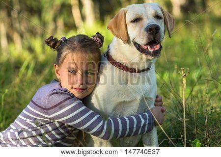 Girlie hugging her dog outdoors.