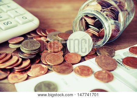 Save money for prepare concept, Coins spilling out of a glass bottle with bill and calculator, Bill for income and expenditure vintage style