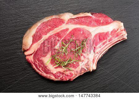 raw rib-eye steak with rosemary on slate background