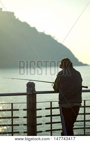 Fisher man waiting on a bridge facing the sea