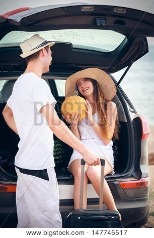 young couple standing near the open car on the seashore
