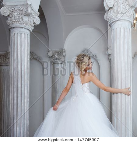 Charming young bride in luxurious wedding dress dancing and spinning around the column