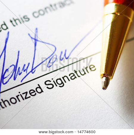 Signing a contract. Shallow depth of field.