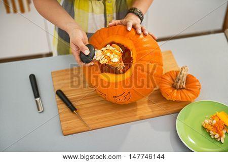 Closeup On Woman Prepare Big Orange Pumpkin For Halloween Party