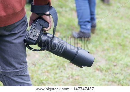Man following another person next to him/her holding a dslr camera. Outdoors on green lawn.