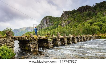 Tourist woman standing on stone slab bridge Terland Klopp in Norway Dalane region.