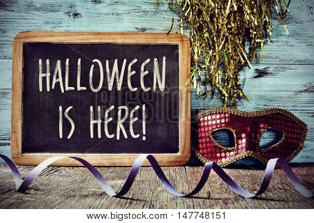 a chalkboard with the text Halloween is here, placed on a rustic wooden surface next to a red and golden carnival mask, and a violet streamer in the foreground