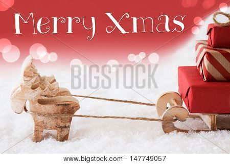 Moose Is Drawing A Sled With Red Gifts Or Presents In Snow. Christmas Card For Seasons Greetings. Red Christmassy Background With Bokeh Effect. English Text Merry Xmas