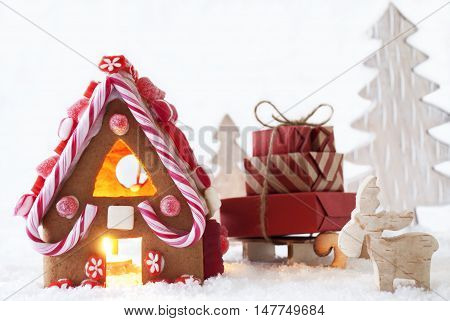 Gingerbread House In Snowy Scenery As Christmas Decoration. Sleigh With Christmas Gifts Or Presents. Christmas Tree And Moose Or Reindeer