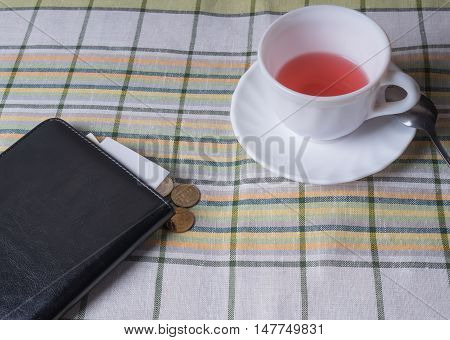 Standing on the table white Cup with tea black folder with the receipt for payment and coins to pay